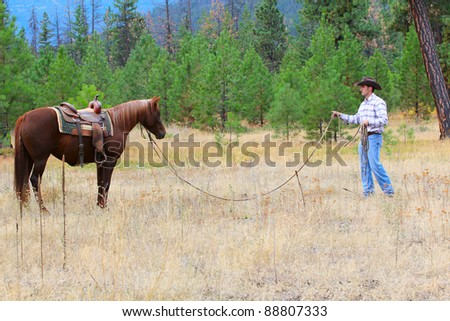 Young cowboy training his horse in the meadows - stock photo