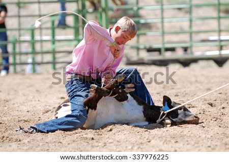 Young cowboy tying the legs of a calf during a rodeo. - stock photo