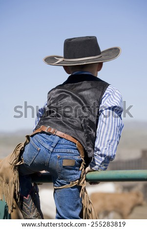 Young cowboy watches the round up from on top of a fence - stock photo