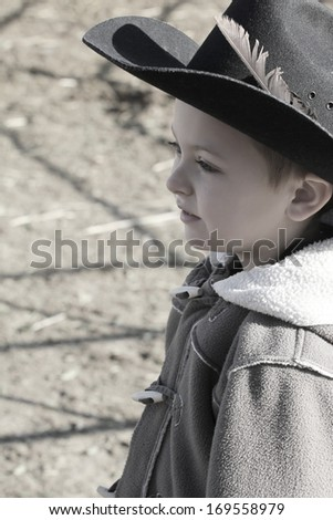 Young cowboy wearing a hat and fleece jacket - stock photo