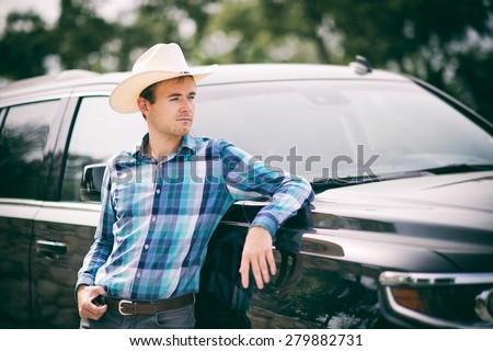 Young cowboy with a hat and his truck - stock photo