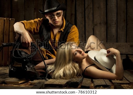 Young cowboy with cowboy girl against wooden background - stock photo