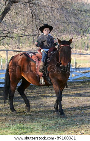 Young cowboy with hat riding his horse - stock photo