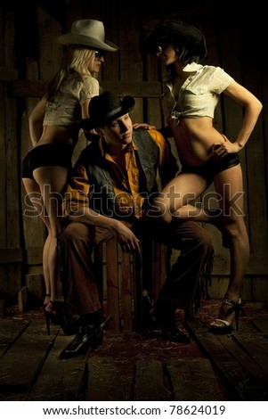 Young cowboy with pair cowboy girls against wooden background - stock photo