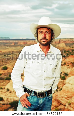 Young cowboy with white hat and shirt standing in desert landscape with cloudy sky, USA. - stock photo