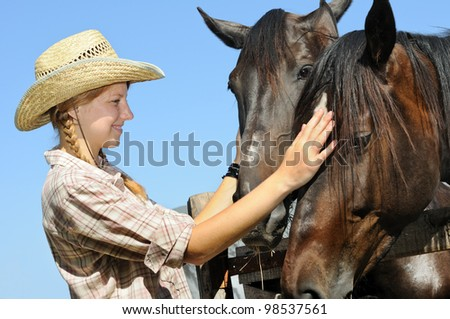 young cowgirl and two horses in the farm