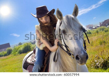 young cowgirl gallop on white horse - stock photo