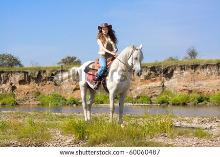 young cowgirl on white horse at the river - stock photo