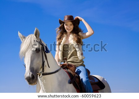 young cowgirl on white horse smile - stock photo