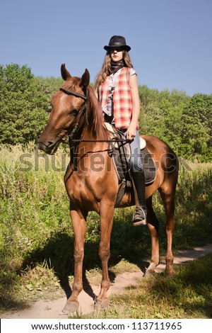 Young cowgirl riding a bay horse - stock photo