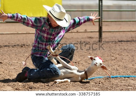 Young cowgirl riding a horse around a barrel in a rodeo. - stock photo