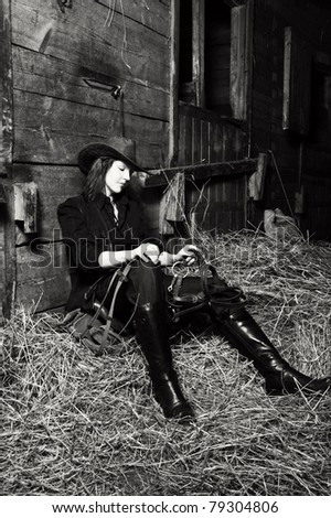 Young cowgirl sitting on hay in the stable