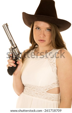 Young cowgirl with a serious facial expression holding a pistol wearing a white sleeveless dress - stock photo