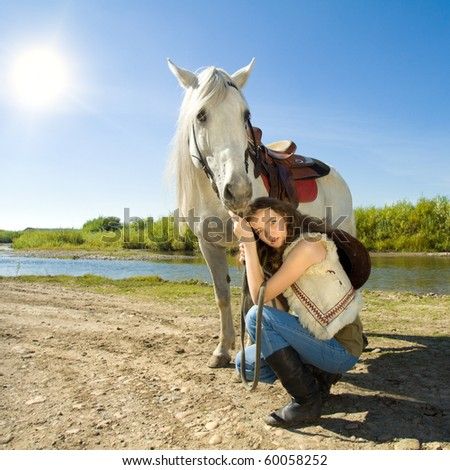 young cowgirl with white horse outdoor - stock photo