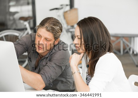 Young coworkers working together and discussing points while using computer - stock photo