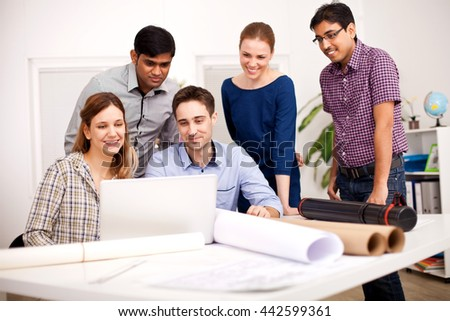 Young coworkers working together on their project  - stock photo