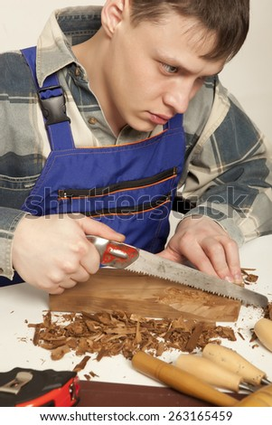Young craftsman in uniform working at carpentry - stock photo