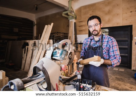 Young craftsman in uniform working at carpentry and looking to camera