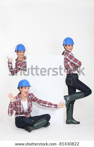 young craftswoman presenting a blank poster - stock photo