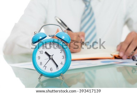 young crazy businessman punching switching off alarm clock sitting at office desk working with computer laptop in deadline project concept and business stress concept - stock photo