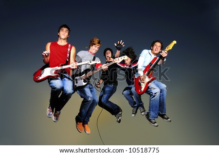 Young crazy gruop of musicians jumping with instruments - stock photo