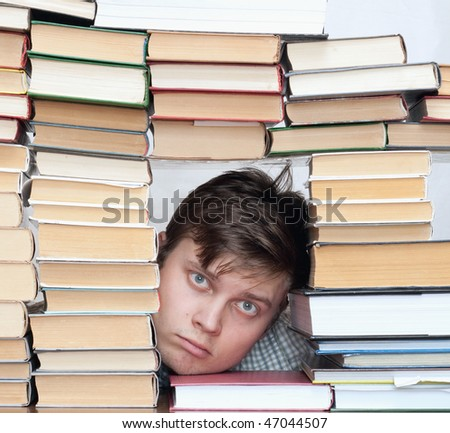 Young crazy tired student between books - stock photo