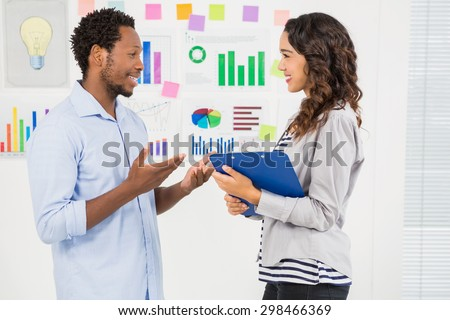 Young creative business people facing each other in the office - stock photo