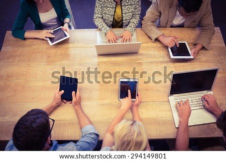 Young creative business people with laptop and digital tablet in the office - stock photo