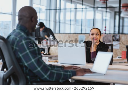 Young creative designers having friendly discussion at office. African american woman sitting at table discussing work with colleague. - stock photo