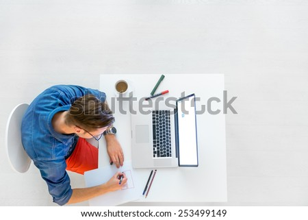 Young creative man writing ideas on paper - stock photo