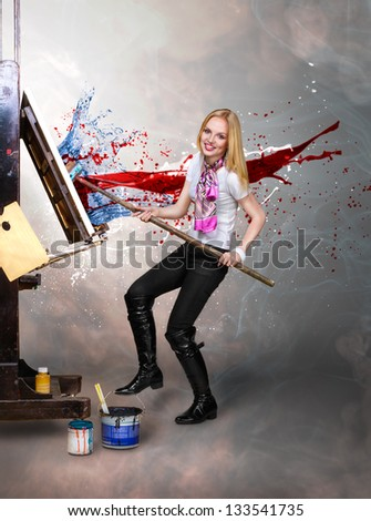 Young creative painter artist blonde woman paint on canvas with big paintbrush - stock photo