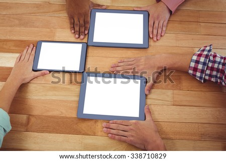 Young creative team using tablets in casual office - stock photo