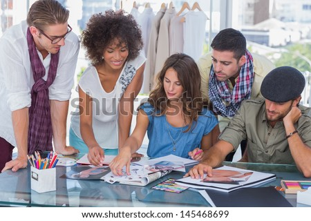 Young creative team working together in a bright modern office - stock photo