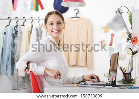 Young creative woman in her office looking at camera./ Fashion woman blogger working in a creative workspace.  - stock photo