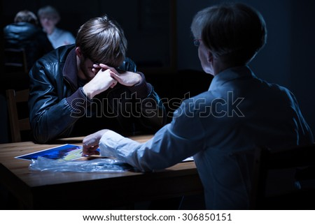 Young crying criminal in police interrogation room - stock photo