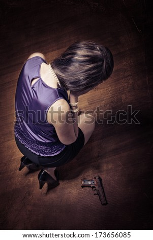 young crying woman with a gun - stock photo