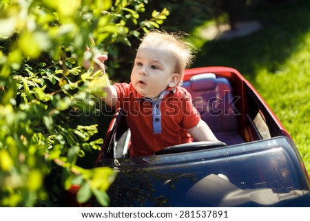 Young curious kid close up portrait with toy car outdoors.