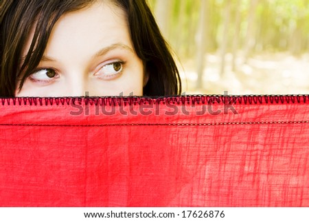 Young curious woman spying behind veil - stock photo