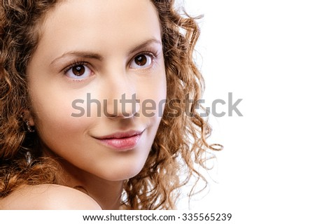 Young curly beautiful woman with bared shoulders smiles, on white background. - stock photo