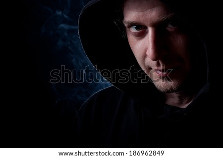 Young curly hair caucasian man wearing black hooded sweatshirt. Low key portrait taken on black background full of smoke.