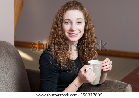 young curly haired Caucasian woman sitting down enjoying a cup of tea