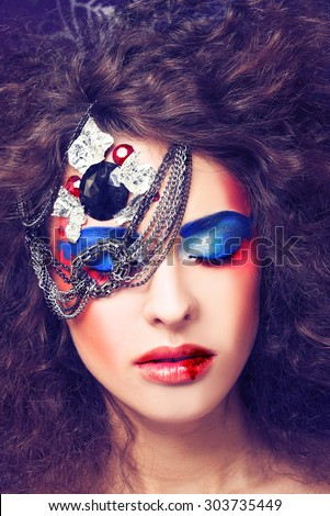Young curly woman with artistic red and blue visage with silver chain