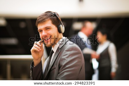 Young customer service operator talking on headset, smiling. - stock photo