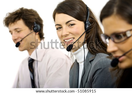 Young customer service representatives sitting in a row and talking on headset, smiling. Isolated on white background. - stock photo