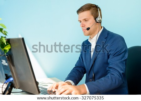 Young Customer Support Phone Operator with Headset Working on Computer in the Office. - stock photo