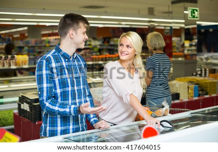 Young customers buying frozen food in supermarket and smiling - stock photo