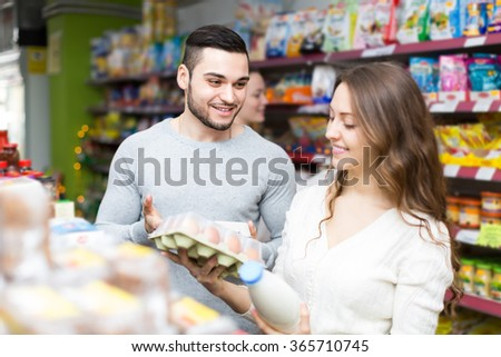 Young customers choosing milk and eggs at store and smiling. Focus on man