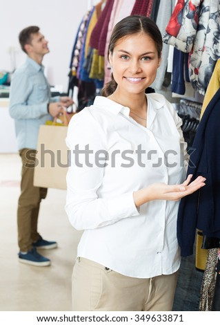 Young customers choosing winter clothes and smiling at the store