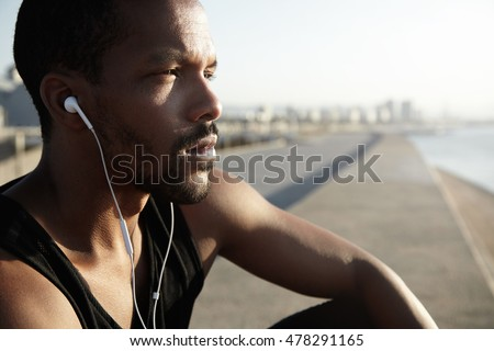 Young cute African American sportsman or jogger contemplating beauty of new day. Attractive black man admiring sunrise listening to music in his earphones, meditating, looking far away, dreaming