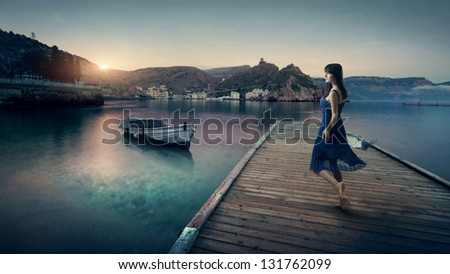 Young cute barefoot girl model in a blue dress on the beach - stock photo